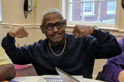 Rodney Reese   Sarcoidosis News   Photo of Rodney sitting at a table with his arms up, flexing his muscles.